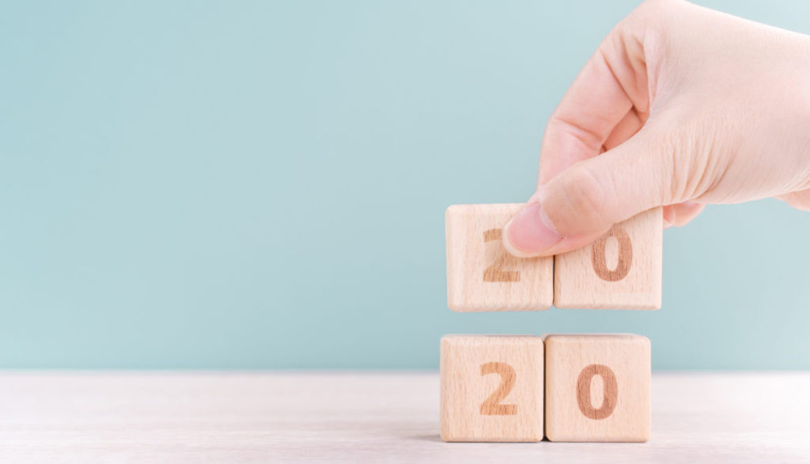 Abstract 2020 & 2019 New year countdown design concept - woman holding wood blocks cubes on wooden table and green background, close up, copy space.